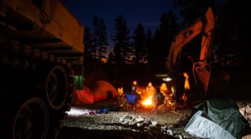 Members of the Raincoast Flying Squad by a camp fire at the forestry road construction blockade north of Port Renfrew, B.C.